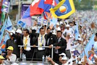 Cambodia National Rescue Party (CNRP) leader Sam Rainsy (C) and other party officials greet supporters in Phnom Penh, on July 19, 2013. Cambodia's newly pardoned opposition leader arrived home from exile to help his party's bid to end Prime Minister Hun Sen's nearly three decades in power
