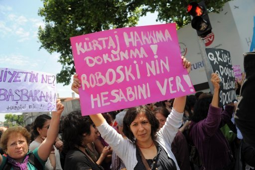 "A Turkish feminist (right) holds a placard reading ""Don't touch our abortion rights"" during a protest outside Prime Minister Recep Tayyip Erdogan's office in Istanbul on May 27. Some 300 women are to protest to the Turkish government Tuesday after Erdogan sparked fury among women's rights advocates by likening abortion to murder."