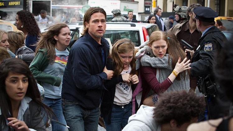 "This publicity image released by Paramount Pictures shows, from center left, Brad Pitt as Gerry Lane, Abigail Hargrove as Rachel Lane, and Mireille Enos as Karin Lanein a scene from ""World War Z."" (AP Photo/Paramount Pictures, Jaap Buitendijk)"