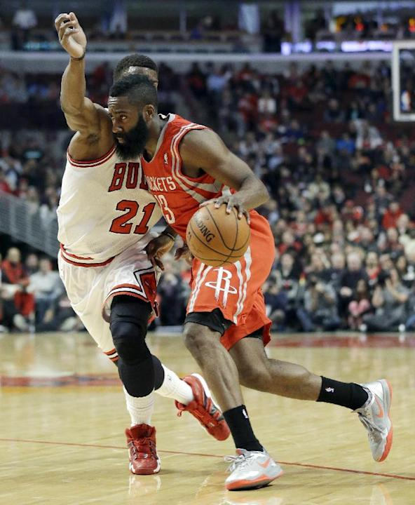 Houston Rockets guard James Harden, right, drives to the basket as Chicago Bulls guard Jimmy Butler defends during the first half of an NBA basketball game in Chicago on Thursday, March 13, 2014