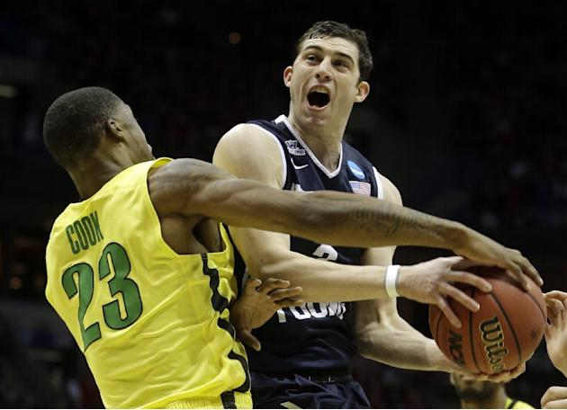 In this March 20, 2014, file photo, BYU guard Matt Carlino, right, is fouled by Oregon forward Elgin Cook (23) during the first half of a second-round game in the NCAA college basketball tournament in