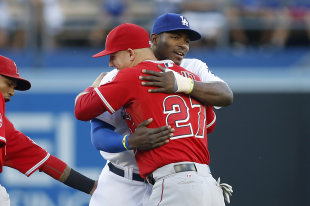 Mike Trout (left) and Yasiel Puig embrace before their game. (AP)
