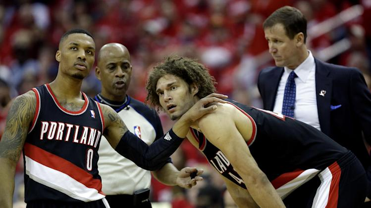 Portland Trail Blazers' Damian Lillard (0) puts his hand on the shoulder of Robin Lopez after Lopez was called for a technical foul against the Houston Rockets during the fourth quarter in Game 1 of an opening-round NBA basketball playoff series Sunday, April 20, 2014, in Houston. The Trail Blazers won 122-120 in overtime