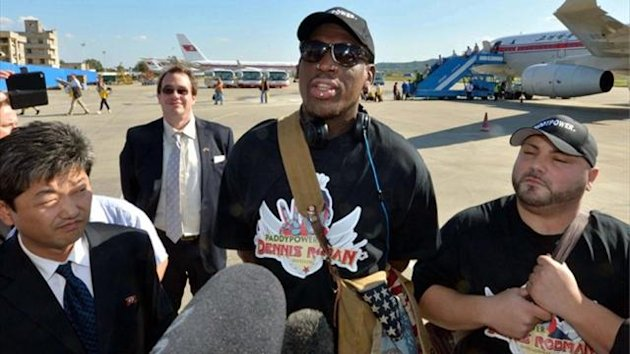 Former basketball star Dennis Rodman (C) arrives at Pyongyang airport (Reuters)