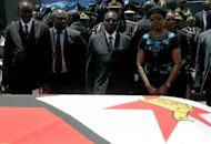 Zimbabwe President Robert Mugabe (centre) looks at the flag-drapped coffin of John Landa Nkomo during funeral ceremony at the National Heroes Acre in Harare, on January 21, 2013