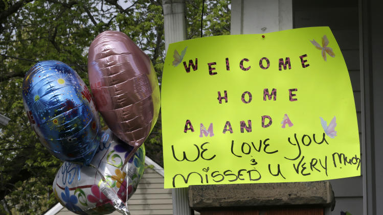 A sign hangs on the porch of the home of Amanda Berry Wednesday, May 8, 2013, in Cleveland. Berry, 27, Michelle Knight, 32, and Gina DeJesus, had apparently been held captive in a house since their teens or early 20s, police said. (AP Photo/Tony Dejak)
