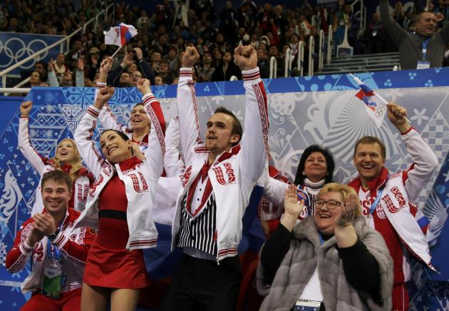 Ksenia Stolbova and Fedor Klimov of Russia react with their teammates during the Team Pairs Free Skating Program at the Sochi 2014 Winter Olympics