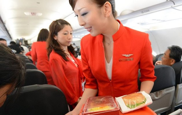 Up in the air: Air Asia Japan's cabin attendants provide the in-flight meal. (AFP photo)