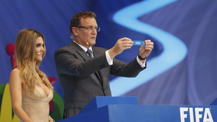 "Valcke holds up the slip showing ""Ecuador"" during the draw for the 2014 World Cup in Sao Joao da Mata"