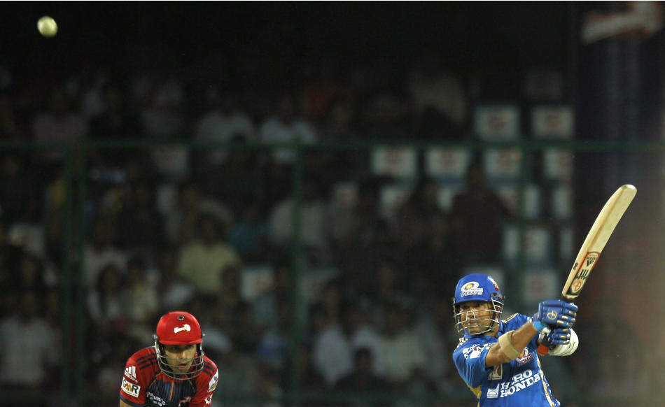 Mumbai Indians' Sachin Tendulkar, right, plays a shot for 6 during the Indian Premier League cricket match against Delhi Daredevils in New Delhi, India, Sunday, April 10, 2011. The fourth edition