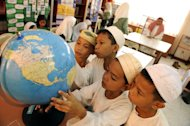 Students look at a globe in the Baseco government elementary school in Manila on October 9, 2008. The Philippines' largest bookstore chain has withdrawn Chinese-made globes showing Beijing's claims to most of the South China Sea from its shelves, a government spokesman said Thursday