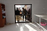 Afghan policemen carry the dead body of a civilian into a hospital morgue following a suicide attack in Khost province, on December 26, 2012