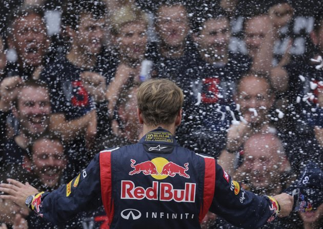 Red Bull Formula One driver Sebastian Vettel of Germany celebrates winning the world championship on the podium with his team after the Brazilian F1 G...
