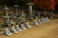 November 24, 2006 shows participants and monks taking meditating sessions during a temple stay at a yard of Mihwangsa temple in Haenam, 350 kms south of Seoul