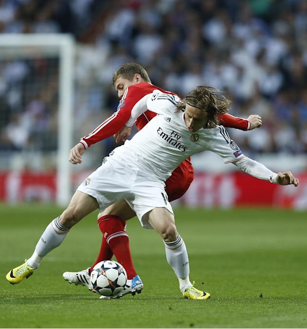 Real's Luka Modric fights for the ball with Bayern's Toni Kroos, during a first leg semifinal Champions League soccer match between Real Madrid and Bayern Munich at the Santiago Bernabeu stadi