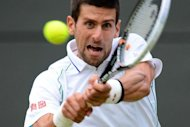 Serbia's Novak Djokovic plays a double-handed backhand shot during his men's singles quarter-final match against Germany's Florian Mayer on day nine of the 2012 Wimbledon Championships tennis tournament at the All England Tennis Club in Wimbledon, southwest London. Djokovic won the match