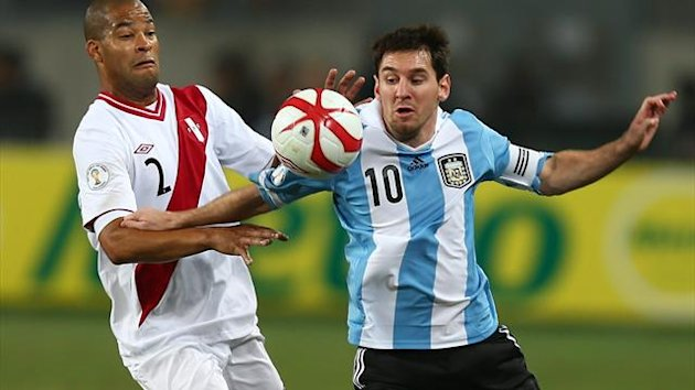 Lionel Messi (R) from Argentina in action against Alberto Rodriguez (L) from Peru during their qualifying match for the World Soccer Championship Brazil 2014