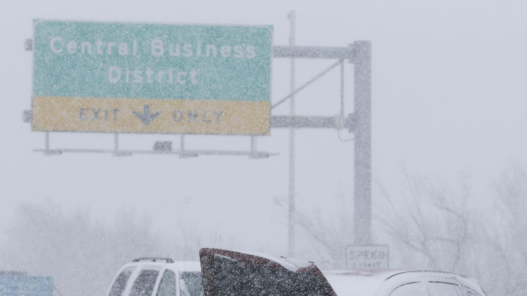 A wrecked car sits in the middle of US Highway 54 near downtown Wichita, Kan. as heavy snow falls on Wednesday morning, Feb. 20, 2013. A large winter storm moved in over the early morning hours and is expected to last until Thursday evening. (AP Photo/The Wichita Eagle, Travis Heying)
