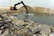 A caterpillar digs reclaimed land from the sea on January 31, 2013, in Lagos, during the building of a three-and-a-half kilometre sea defence barrier that will shield Eko Atlantic from erosion.