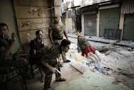 Free Syrian Army fighters man a position in the Old City of Aleppo. Fighting raged in Syria's two biggest cities on Sunday as UN-Arab League envoy Lakhdar Brahimi ended his first visit to the country on a peace mission a rebel commander said was doomed to fail