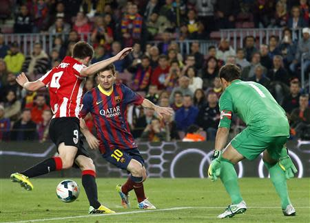 Barcelona's Lionel Messi vies for the ball against Athletic Bilbao's goalkeeper Gorka Iraizoz and Aymeric Laporte during their La Liga soccer match at Camp Nou stadium in Barcelona