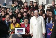 "Pope Francis poses with members of musical group ""Up with People"" during his Wednesday general audience in Saint Peter's square at the Vatican December 18, 2013. REUTERS/Tony Gentile"