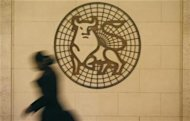 A woman walks past the Merrill Lynch logo outside their offices in the City of London