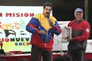 Venezuela's President Nicolas Maduro (L) shows a picture of a metro tunnel wall with an image which he says is the face of late President Hugo Chavez, in Caracas October 30, 2013. REUTERS/Miraflores Palace/Handout via Reuters