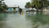 "Residents wade through flooding caused by high ocean tides in low-lying parts of Majuro Atoll, the capital of the Marshall Islands, on February 20, 2011. The Marshall Islands has warned of a Pacific ""climate catastrophe"" that will wipe it off the map without decisive action on global warming, saying the next 12 months are critical"