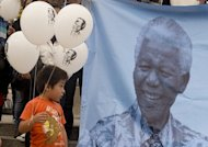 A boy looks at a picture of former South African president Nelson Mandela during an event to mark Mandela Day in Mexico City on July 18, 2013. Mandela entered a seventh week in hospital on Friday, the day after his 95th birthday was marked by millions of people around the world, heartened by news that the anti-apartheid icon is showing signs of improvement