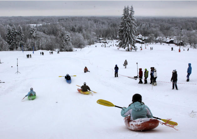 People compete during a snow kayak downhill race near Otepaa