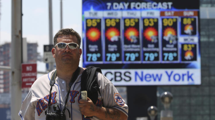 Ricky Otazu, of Lodi, N.J. walks past a giant screen outside the Jacob K. Javits Convention Center announcing the week's weather forecast, Tuesday, July 16, 2013, in New York. Temperatures in the New York metropolitan area are expected to stay in the 90s through Saturday. (AP Photo/Mary Altaffer)