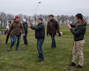 Protesters try to play on a golf course at the Ukrainian…