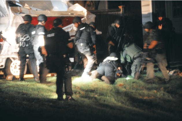 In this Friday, April 19, 2013 photo provided by the Massachusetts State Police, law enforcement officials apprehend Boston Marathon bombing suspect Dzhokhar Tsarnaev at the time of his capture in Wat