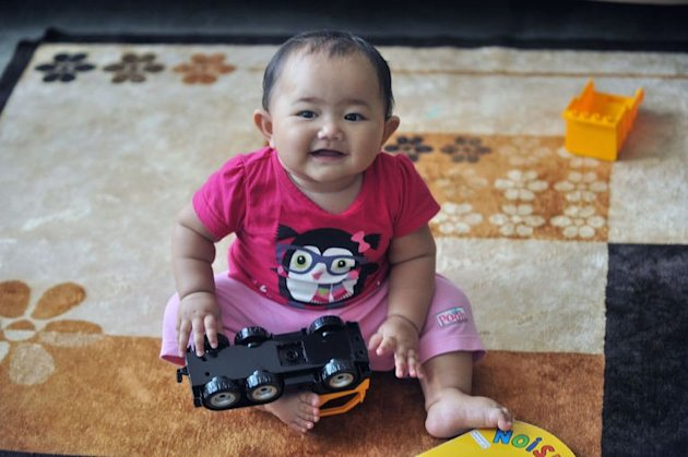 A young Singaporean baby plays at her home in Singapore on January 21, 2013. Singapore announced increased cash bonuses for parents of newborn babies and introduced paternity leave as part of a package of measures to boost population and reduce dependence on foreigners