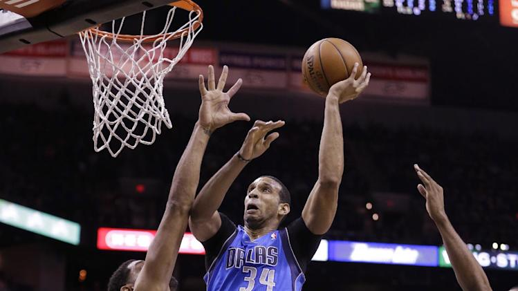 Dallas Mavericks' Brandan Wright (34) shoots over San Antonio Spurs' Tim Duncan, left, during the second half of Game 1 of the opening-round NBA basketball playoff series, Sunday, April 20, 2014, in San Antonio. San Antonio won 90-85