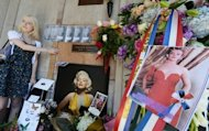 A Marilyn Monroe fan pays her respects at the crypt where the star lays before a memorial service to mark the 50th anniversary of her death at Westwood Village Memorial Park Cemetery in Los Angeles on August 5