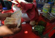 A shopkeeper counts rupee notes at a roadside food stall in Mumbai on May 7. India's central bank on Thursday announced new measures to stem the recent fall in the rupee, which a day earlier posted its lowest-ever finish against the dollar on growing eurozone concerns
