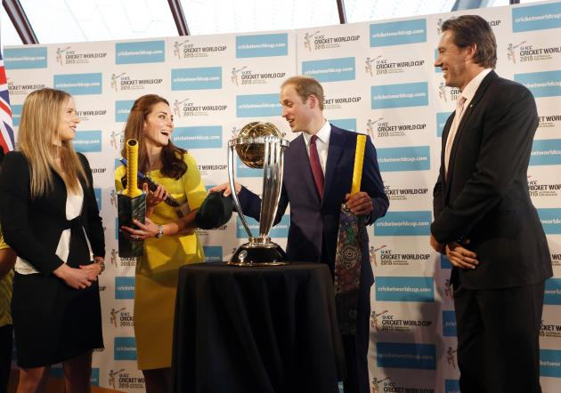 Britain's Prince William and his wife Catherine, Duchess of Cambridge, hold cricket bats presented to them near the Cricket World Cup trophy at the Sydney Opera House