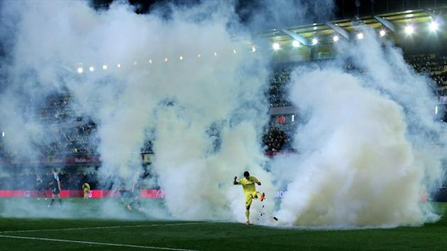 Villarreal's forward Jonathan Pereira kicks a smoke bomb thrown onto the field during the Spanish league football match Villarreal vs Celta de Vigo at El Madrigal stadium in Villareal on February 15, 2014. AFP