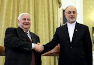 Iranian Foreign Minister Ali Akbar Salehi (right) shakes hands with his Syrian counterpart Walid al-Muallem ahead of a press conference in Tehran, on March 2, 2013. Salehi says Tehran expects Bashar al-Assad to remain Syria's president until elections next year.
