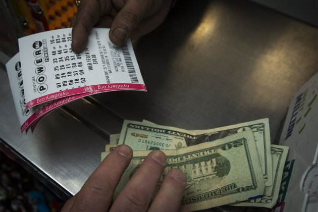 A man purchases New York State Lottery tickets for the Powerball lottery in New York. (Reuters)