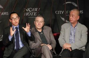 Ho, Co-chairman and CEO of Melco Crown Entertainment Limited, gestures next to actor De Niro and celebrity chef Matsuhisa during a news conference in Manila