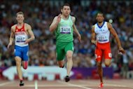 Ireland's Jason Smyth (C) crosses the line to win gold ahead of Russia's Alexander Zverev (L) and Cuba's Luis Felipe Gutierrez (R) in the men's 200m - T13 final during the athletics competition at the London 2012 Paralympic Games on September 7, 2012