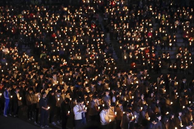 "Students from Danwon high school and other people attend candlelight vigil to wish for safe return of missing passengers from South Korean ferry ""Sewol"", which sank in the sea off Jindo, in"