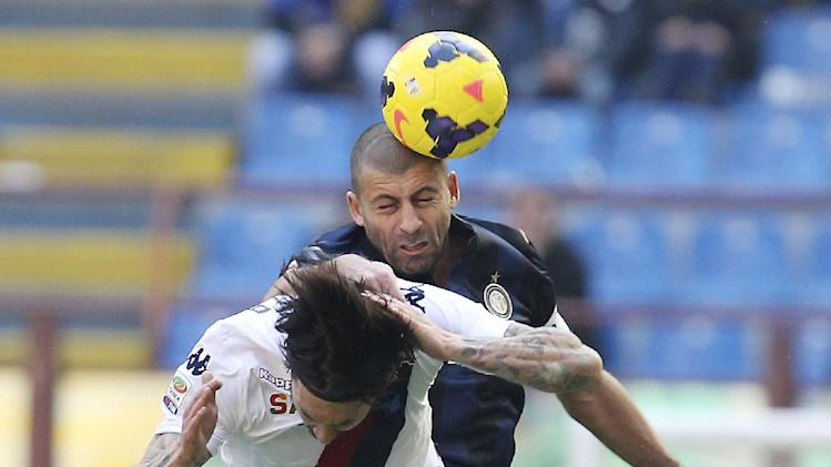 Inter Milan Argentine defender Walter Samuel, top, jumps for the ball with Cagliari forward Mauricio Pinilla, of Chile, during the Serie A soccer match between Inter Milan and Cagliari at the San Siro stadium in Milan, Italy, Sunday, Feb. 23, 2014