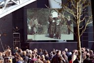People watch the remembrance service on a large screen in Lommel, Belgium, for the local victims of last week's bus crash in Switzerland, on March 21, 2012. Belgium's king and the Dutch crown prince joined thousands of mourners in a highly emotional homage Wednesday to the victims of last week's fatal school bus crash in a Swiss alpine tunnel