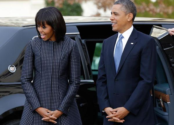 President Barack Obama and first lady Michelle Obama react as they watch their daughters as the first family arrives at St. John's Church in Washington, Monday, Jan. 21, 2013, for a church service during the 57th Presidential Inauguration. (AP Photo/Jacquelyn Martin)