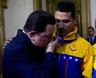 Venezuelan President Hugo Chavez (L) kisses the London 2012 Olympic Games gold medal of Venezuelan fencer Ruben Limardo, in Caracas on August 7, 2012. AFP PHOTO/JUAN BARRETO