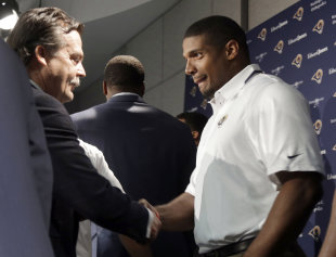 Michael Sam shakes hands with coach Jeff Fisher during a news conference in May. (AP)